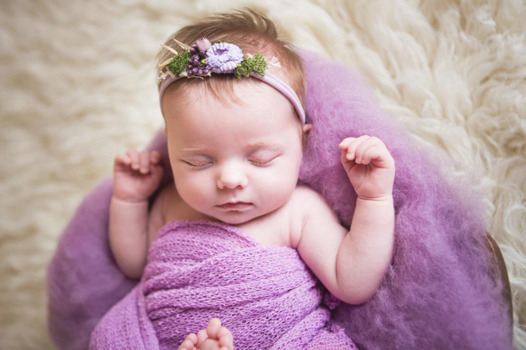 Beautiful baby in purple lying in a bowl