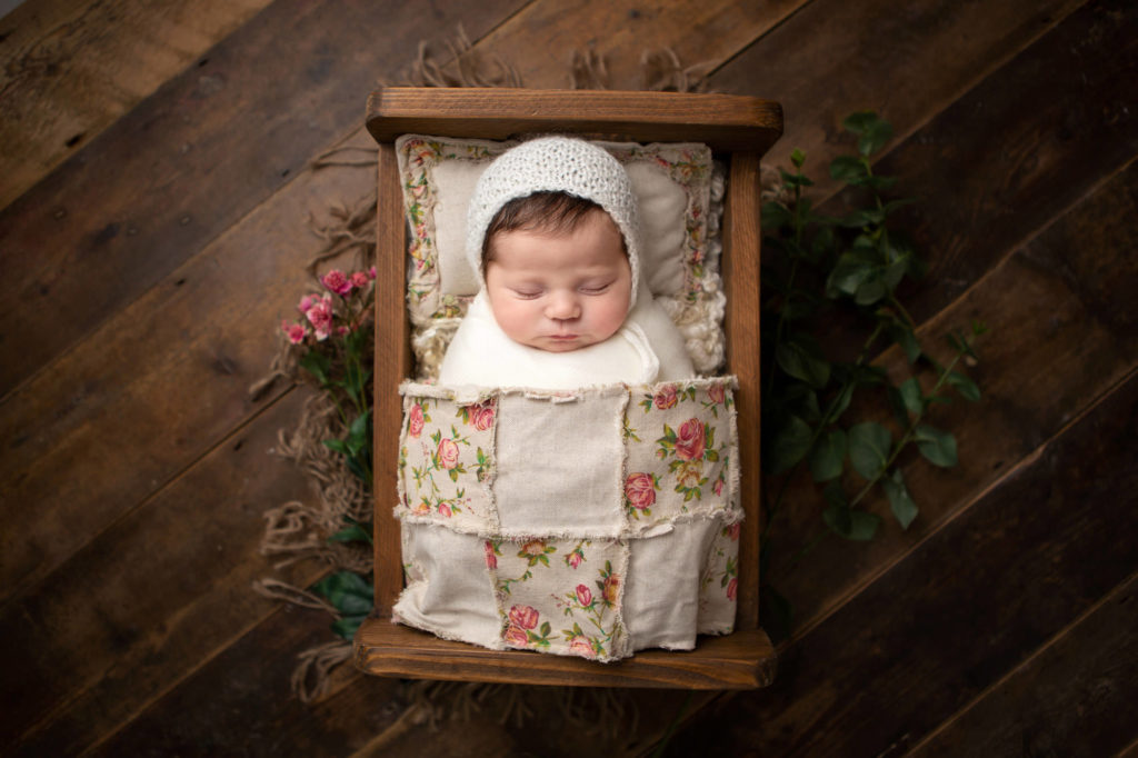 Baby girl in a bed wearing a cream bonnet, Caerphilly Newborn Photographer