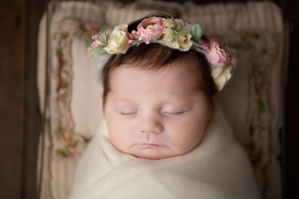 close up picture of a baby girl with a flower halo on asleep on a pillow