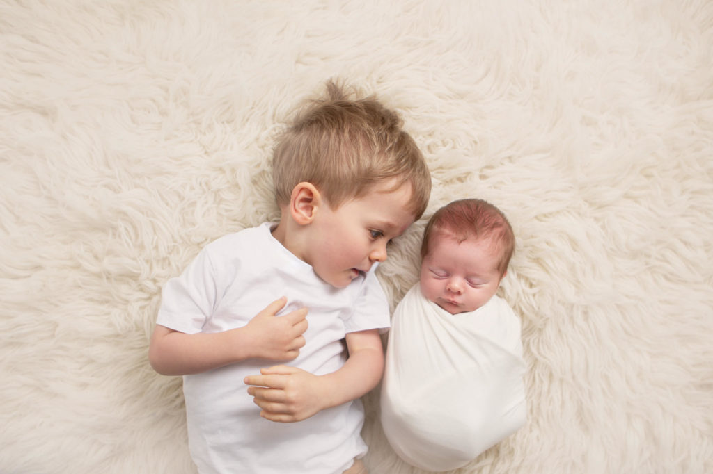 Two brothers asleep on a cream rug -Caerphilly Photographer