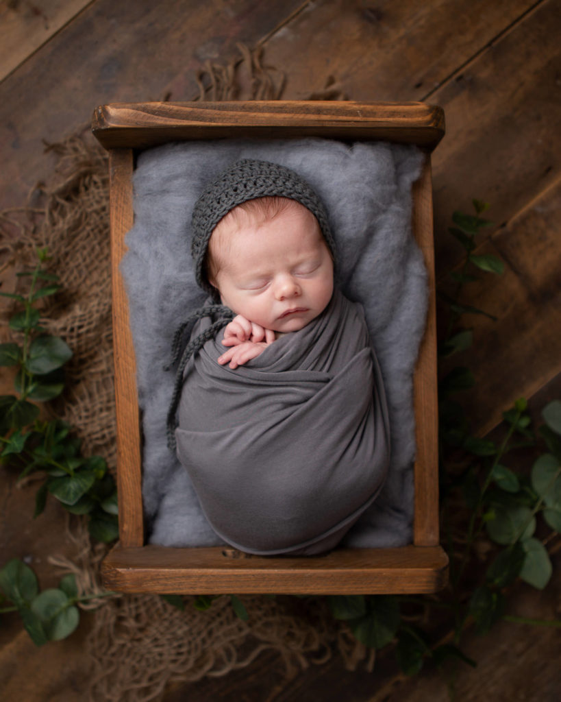 Baby boy wrapped in grey asleep in a little bed prop -Caerphilly Photographer