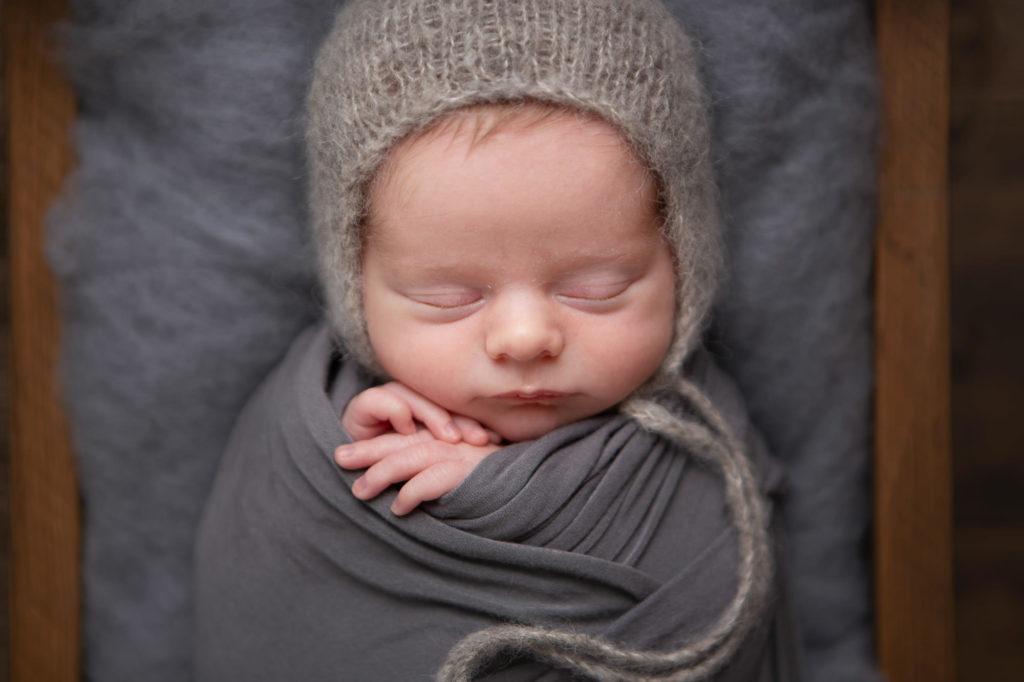 Close up of a newborn baby boy in a grey bonnet