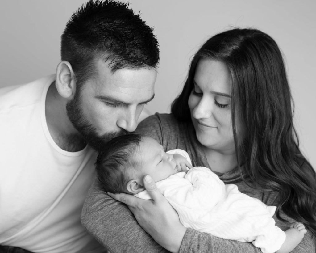 Proud mummy & daddy kissing their baby at a newborn shoot in Caerphilly
