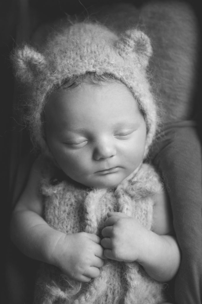 A newborn baby in a black and white photo with teddy bonnet on