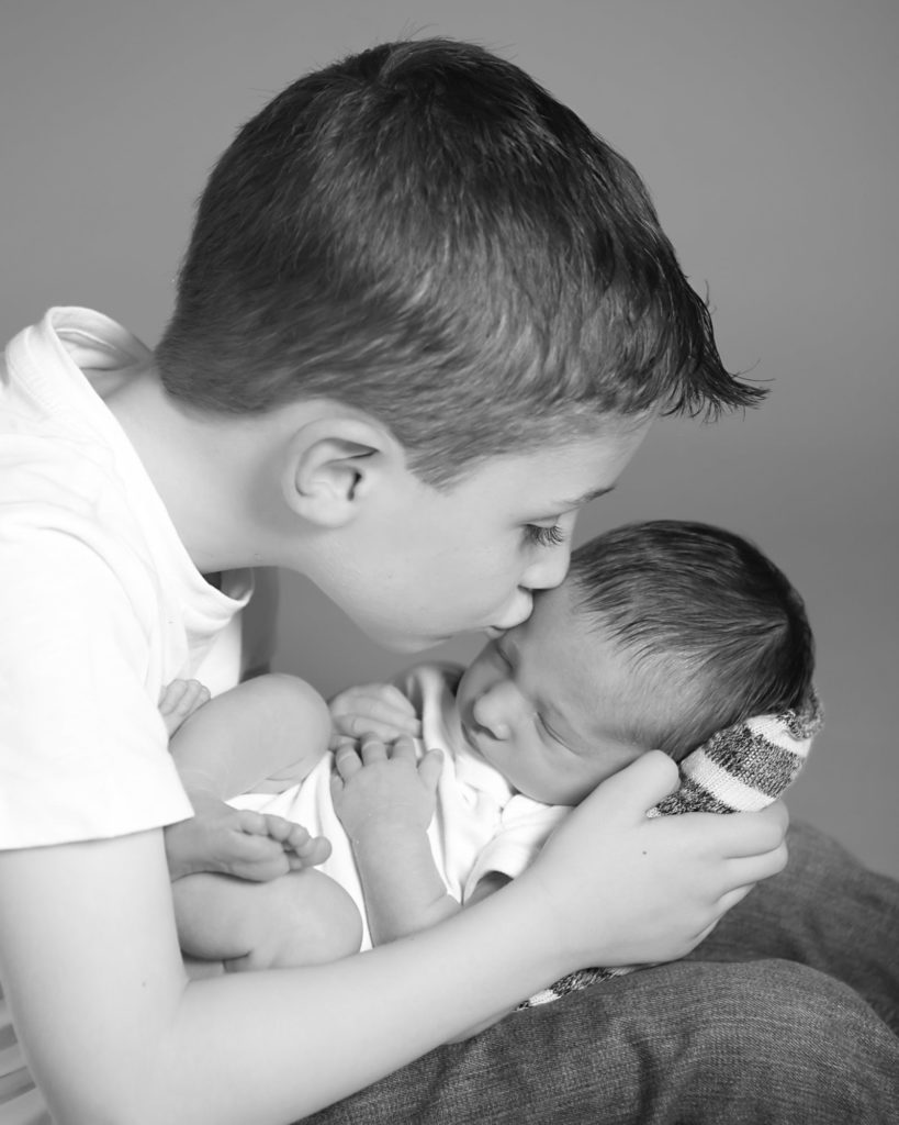Big brother kissing his new baby brother while hold ing him on his lap.