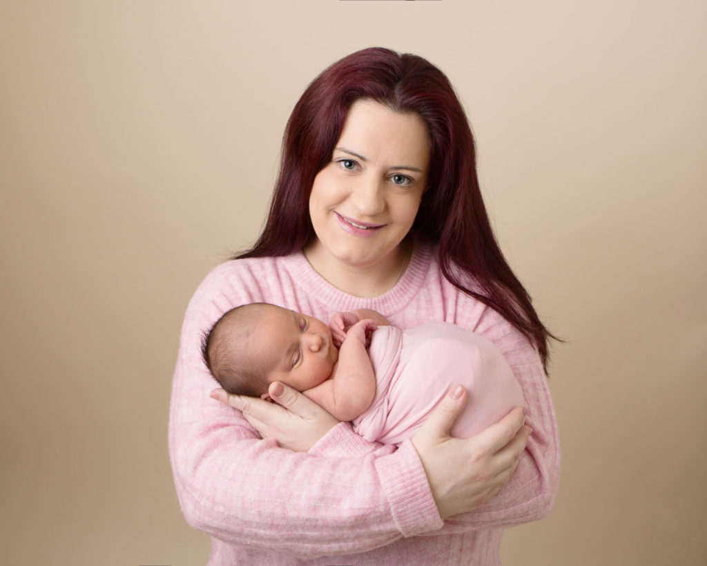 Mother holding baby and smiling at their newborn photoshoot in Caerphilly