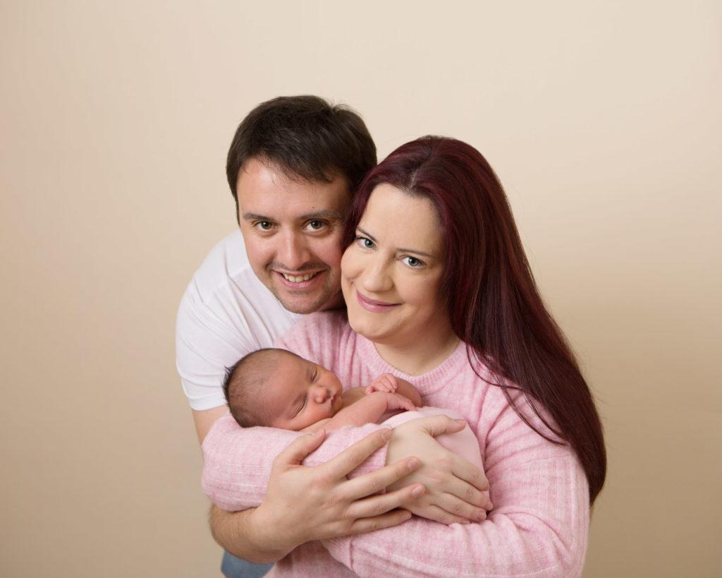 Mum and Dad holding their newborn baby at their newborn photoshoot in Caerphilly Studio
