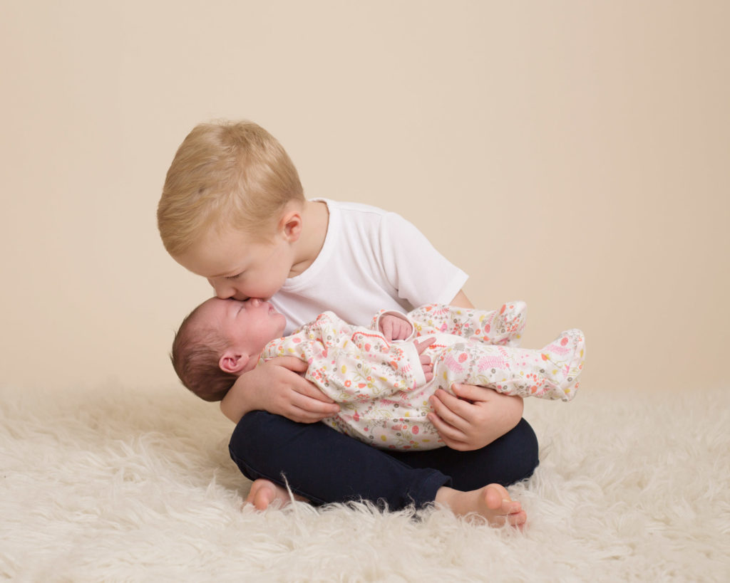 brother kissing his new sister at their newborn photoshoot in Caerphilly