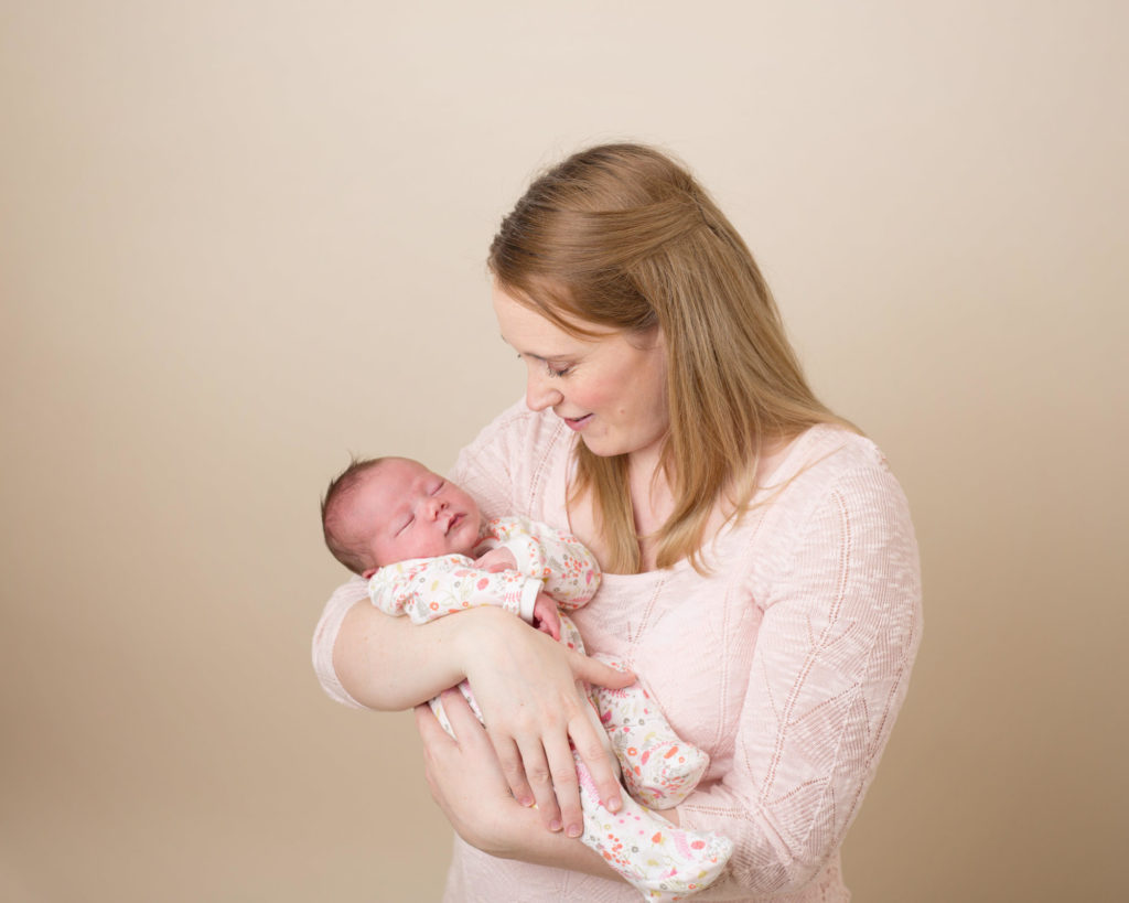 Mother holding her newborn baby during a newborn photoshoot in Caerphilly
