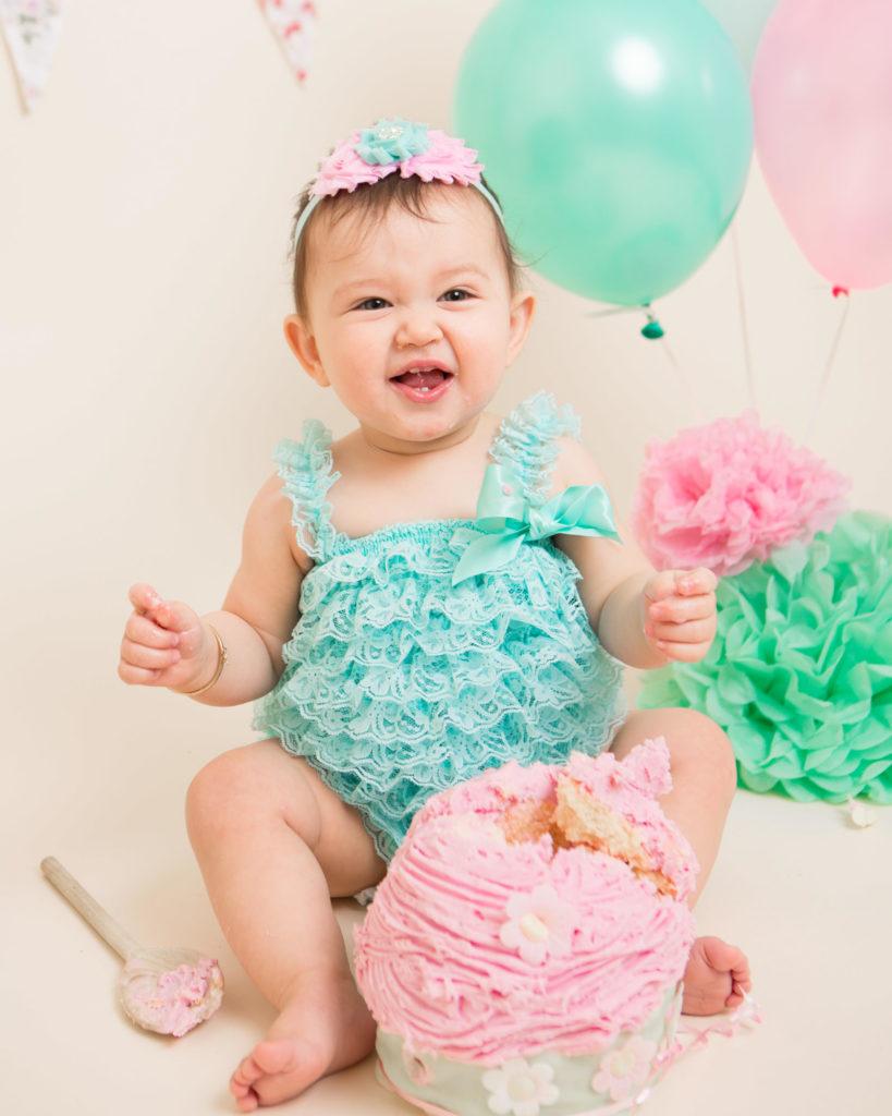 A happy girl smashing her pink cake