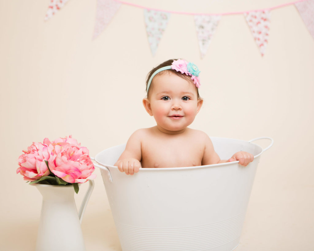 An adorable little girl holding onto the side on a white tub