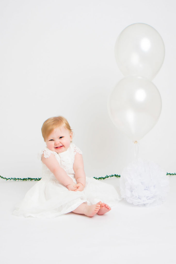 A pretty girl smiling with white balloons next to her