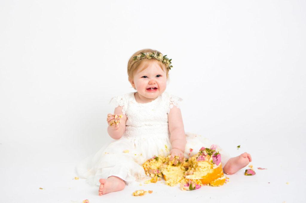 a little girl dressed in white smashing her cake