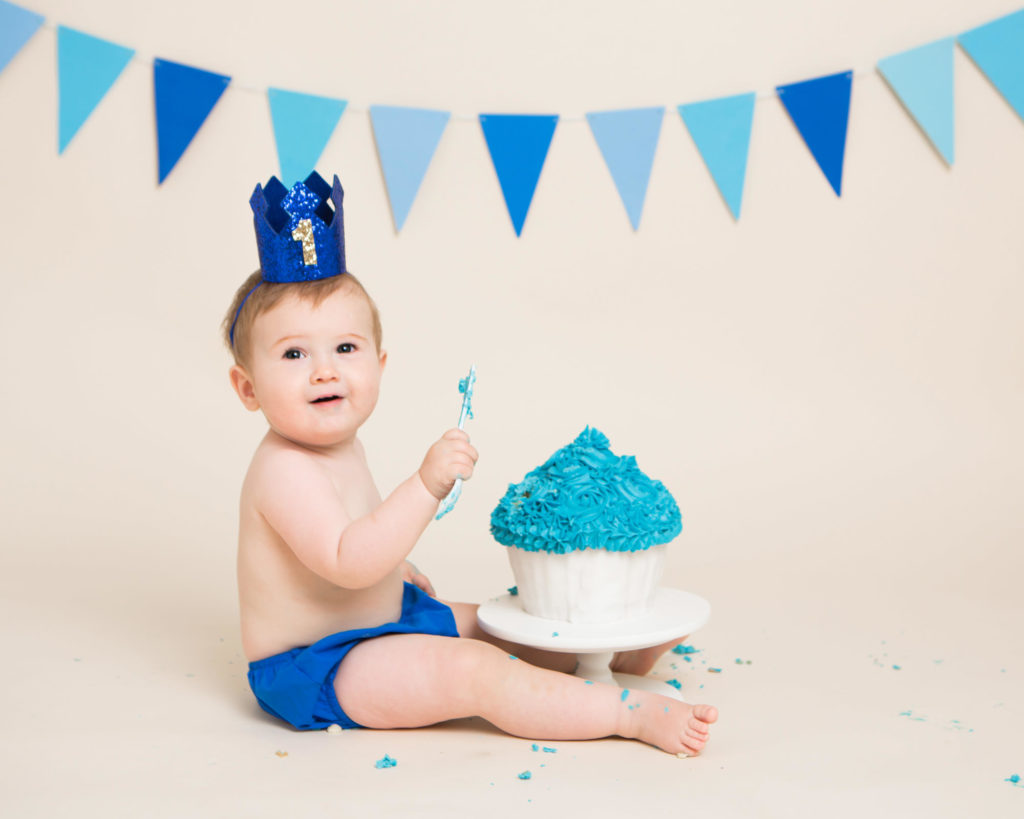 A little boy holding a spoon ready to eat his blue cake