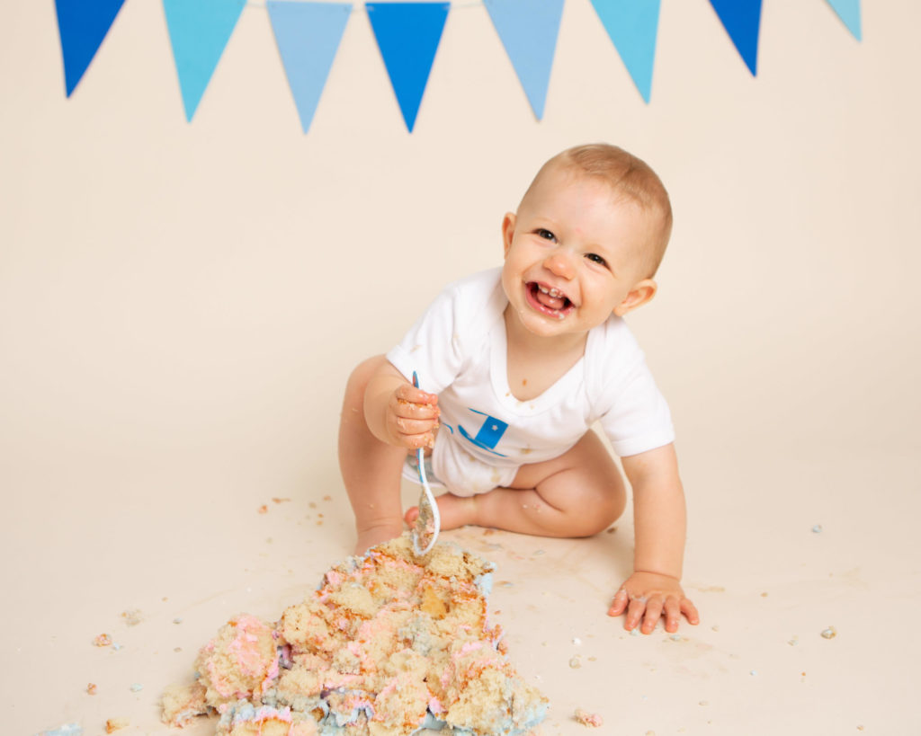 A boy smiling while he smashes his cake