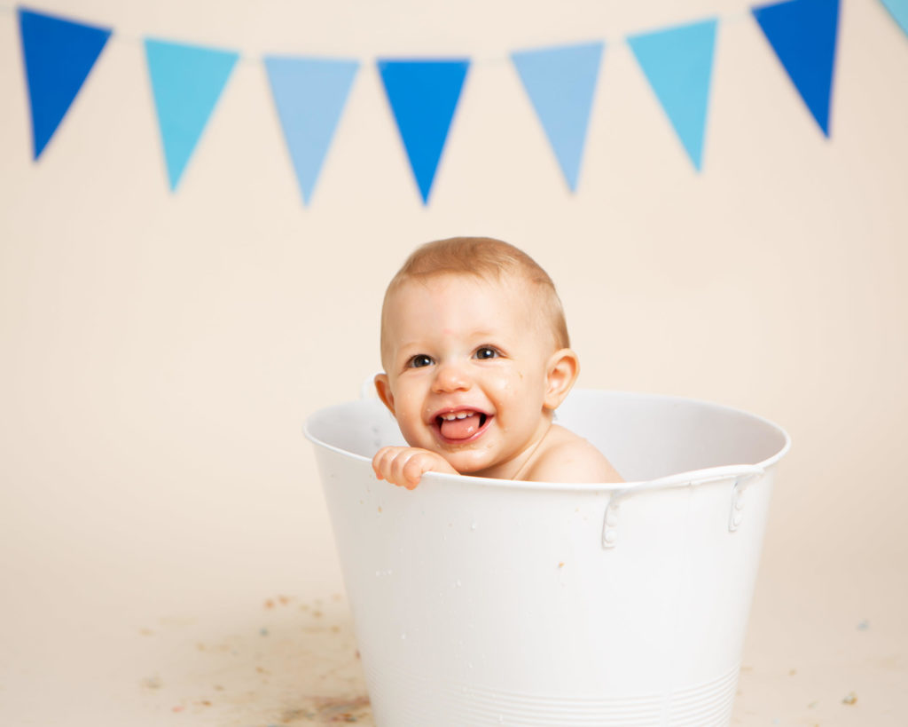 Cute boy in have a splash in the tub after his cake smash