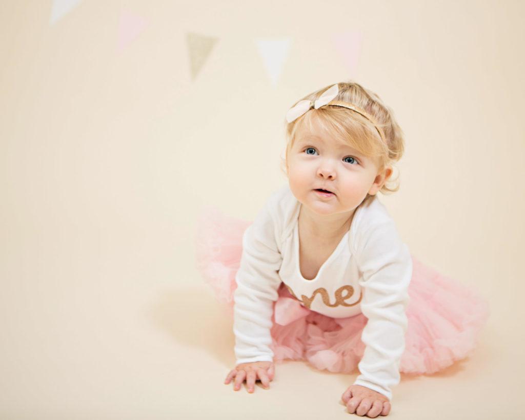 A little girl crawling forward wearing a pink tutu