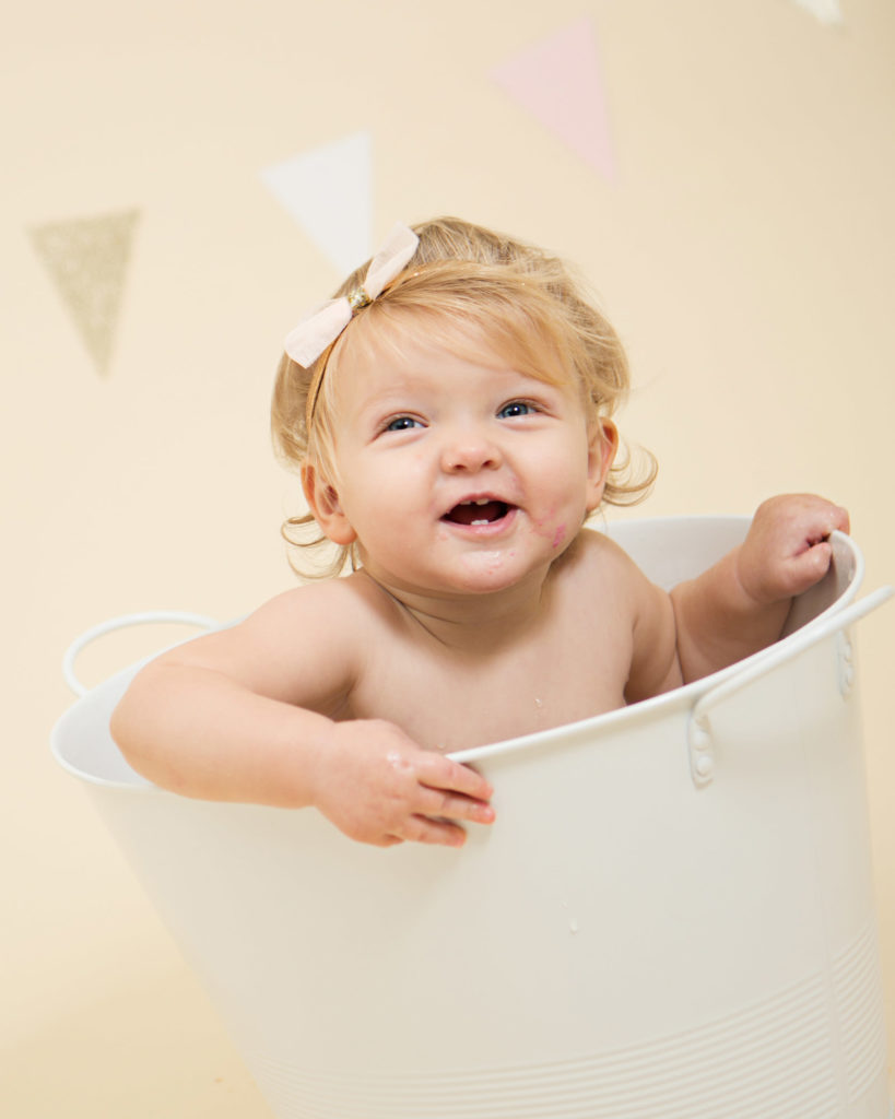 A big grin from a blonde hair girl in a tub