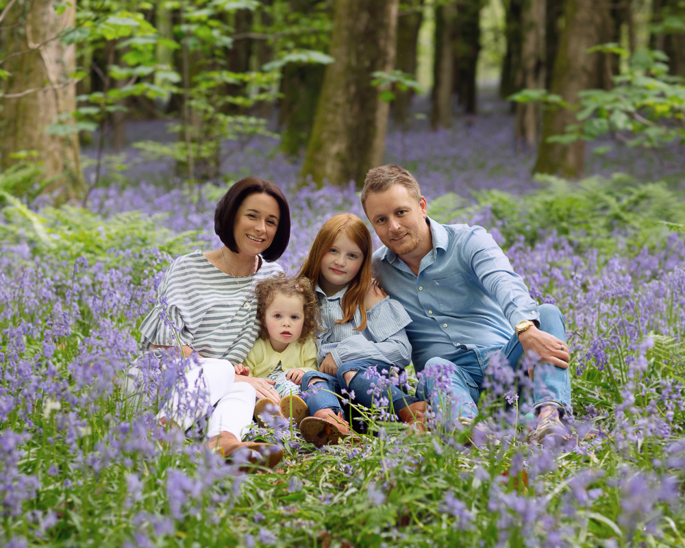 family sitting in the bluebells