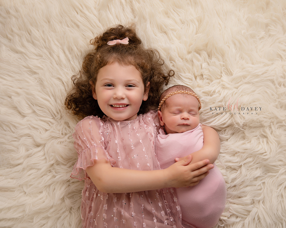 Sisters lying down on a cream rug, big sister is smiling hugging her new baby sister