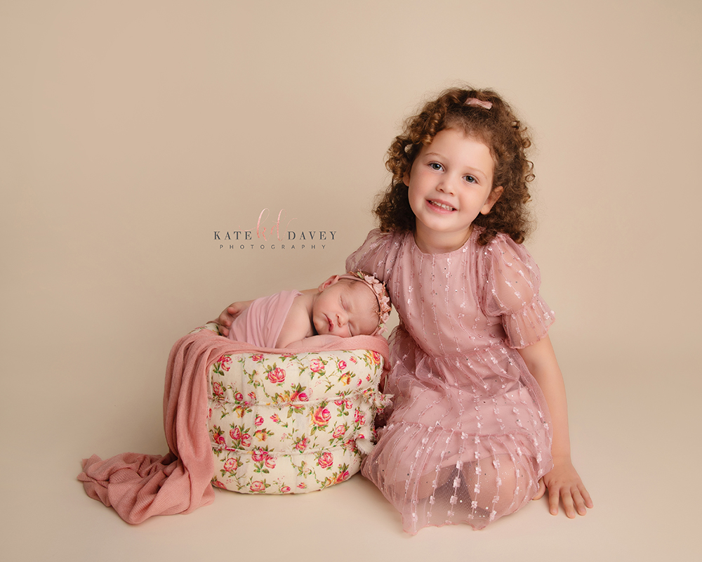 Sister sitting together on a cream backdrop, baby is in a flower basket